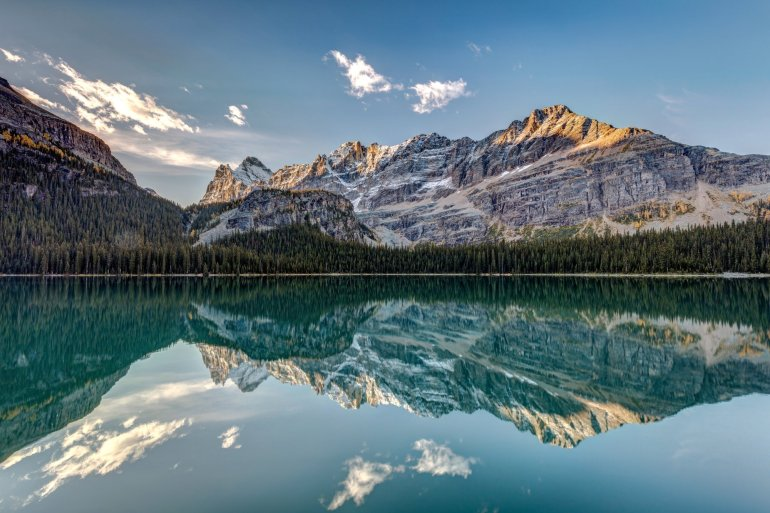 An alpine lake reflects the rocky mountains behind it.