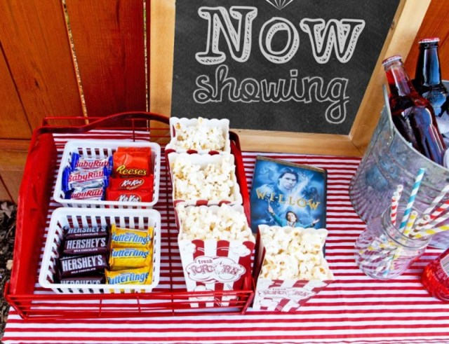 A staycation idea for kids movie night snacks, popcorn, chocolate candy, a DVD, soda in glass bottles, and a movie sign.