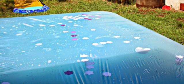 Large blue water blob with purple plastic flowers inside it. Photo credit, Kent Heartstrings.
