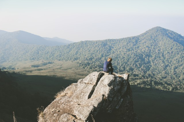 Man sitting on top of a cliff looking at green mountains in the distance.