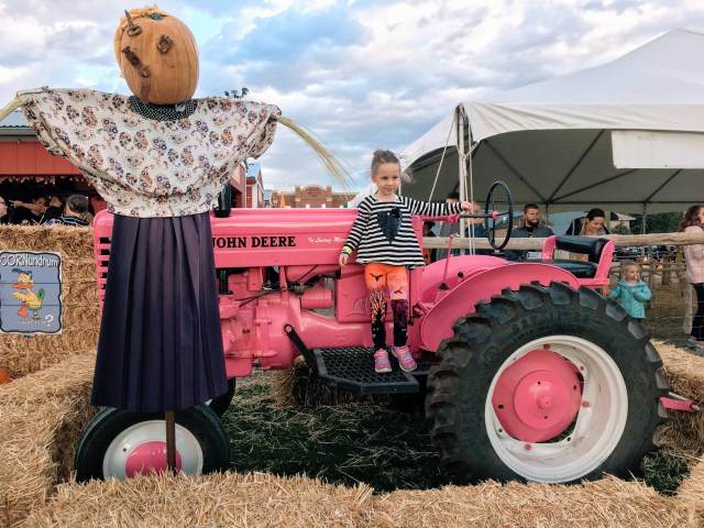 Pink John Deere tractor with a little girl on it and a scarecrow next to it surrounded by haystacks. Used to show the best places to visit in the fall.