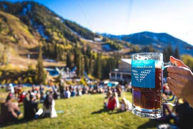 Up close of a mug of beer with blurred background of people sitting on the grass with mountains in the background.