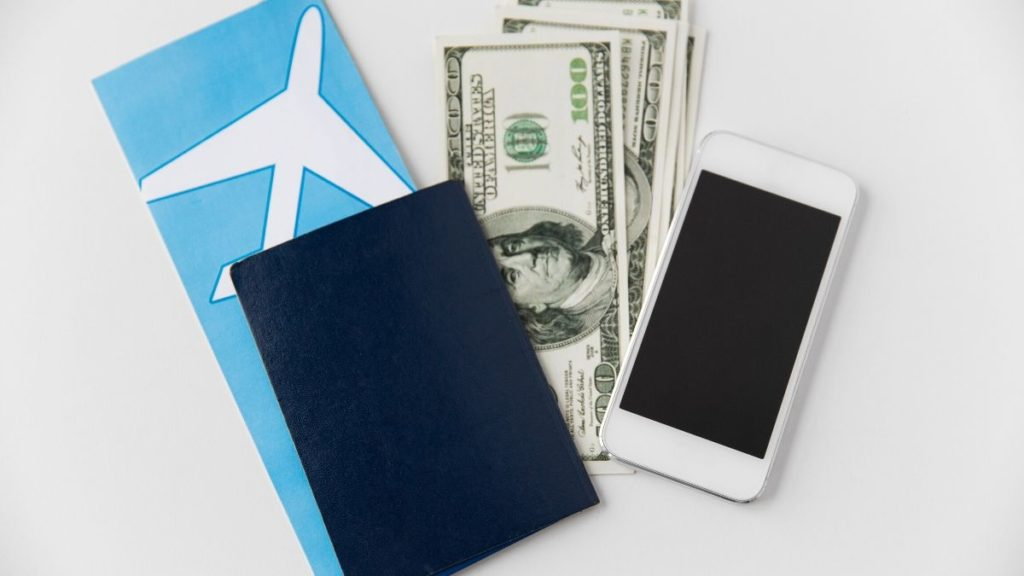 picture of a passport, phone,  and money some of the things you must pack in your Carry-On