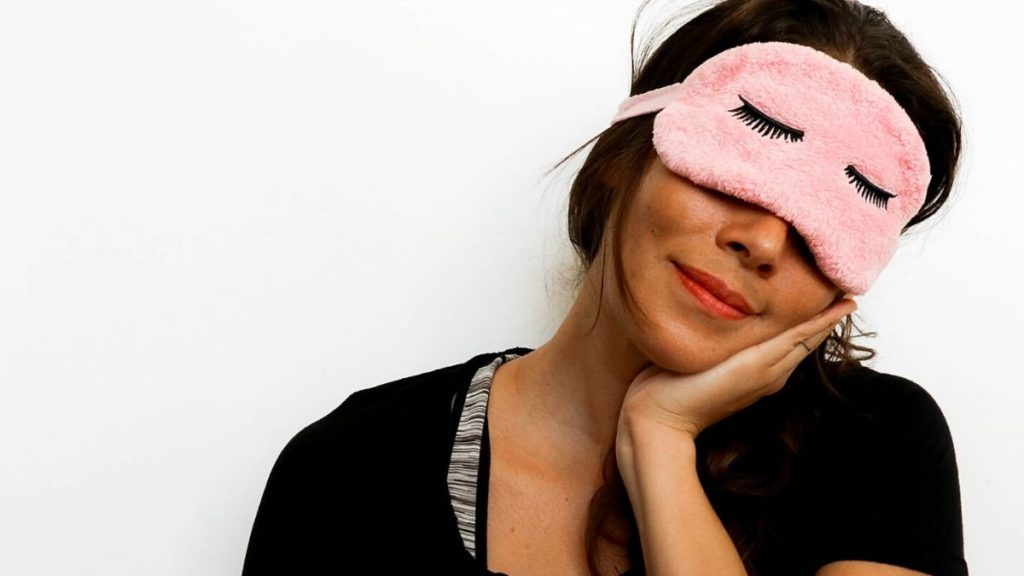 Me posing with a sleeping mask over my eyes and pretending to be asleep
