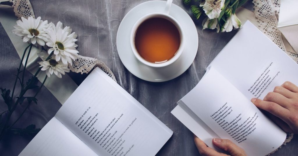 Picture of a cup of tea with someone reading a book