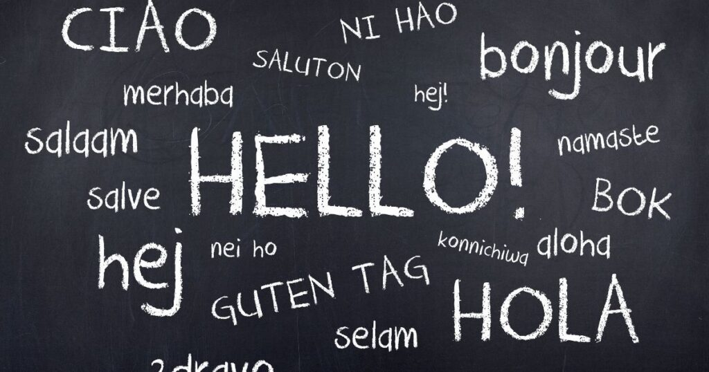 blackboard with hello written in various languages. Learning a language is one of the things to do at the airport.