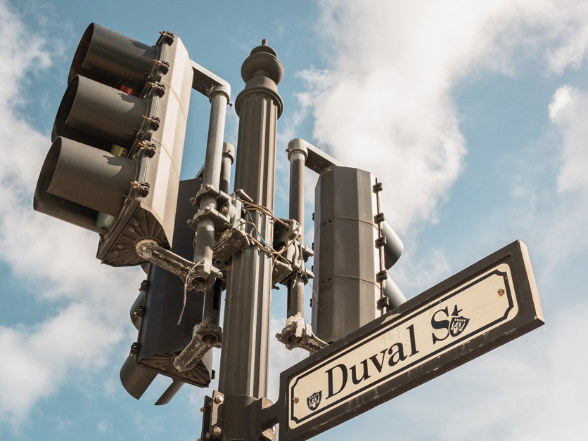 Picture of a stop light with the Duval Street sign. Walking Duval Street is one of the top things to do in Key West.