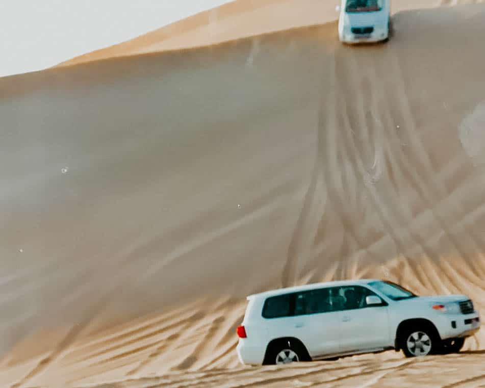 cars going down a sand dune during my Abu Dhabi day trip from Dubai