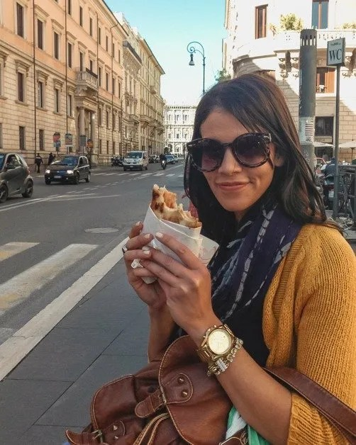 Me posing with a delicious pizza in my hand in Rome an awesome solo female travel destinations