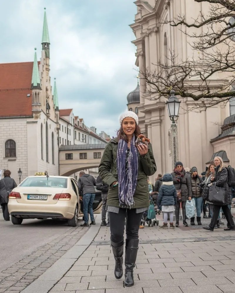 Picture of me holding a pretzel in Old Town Hall in Munich an awesome city for solo female travel