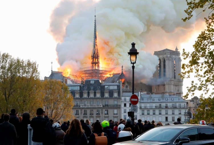 Seen from across the Seine River, smoke and flames rise during a fire at the landmark Notre-Dame Cathedral in central Paris on April 15, 2019, potentially involving renovation works being carried out at the site, the fire service said. Francois Guillot | AFP | Getty Images