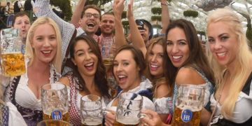 People drink the first mugs of beer after the official opening of the 184th Oktoberfest.PHOTO: AFP