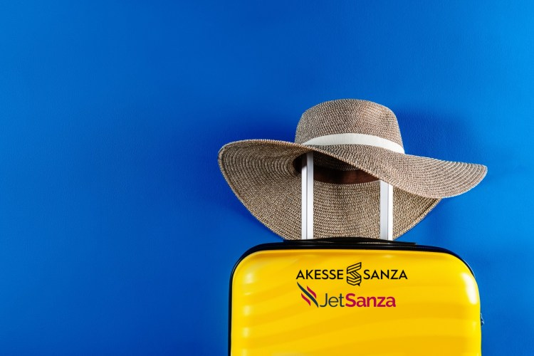 Bright and stylish yellow cabin size suitcase with straw hat against trendy blue background. Easy travel with little baggage concept. Copy space.