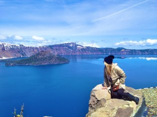 """Laura rocks a comfy Baja pullover at Crater Lake in Oregon. The patterned hoodie is practically a right of passage for the boho traveler. For style that says, """"I woke up like this,"""" and not, """"I smell like…(you know),"""" pair the pullover with some dark skinny jeans and boots. Avoid a light jean or shabby pant, unless you're going for the Kurt Cobain look (still hot). Keeping things chic on the bottom is the way to go. Shop Laura's look."""