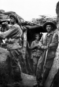 A black and white photograph of men wearing military uniforms in a trench. One man stands on a parapet looking away to the left, while others behind him stare into the camera