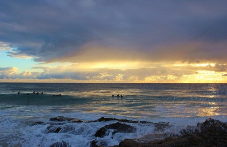 Surfers at sunrise at Snapper Rocks in Coolangatta, Gold Coast, Australia