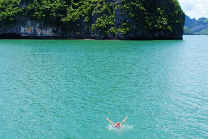 Sarah swimming in the pale blue water of Halong Bay in Vietnam