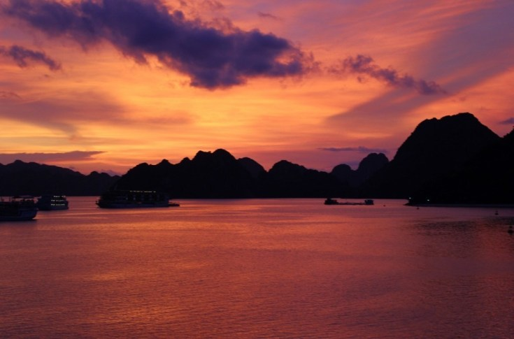 Orange sunset lit the sky and water on Halong Bay, Vietnam