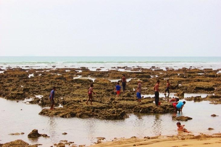 Kids play on exposed rocks at low tide on Klong Khong Beach in Koh Lanta, Thailand