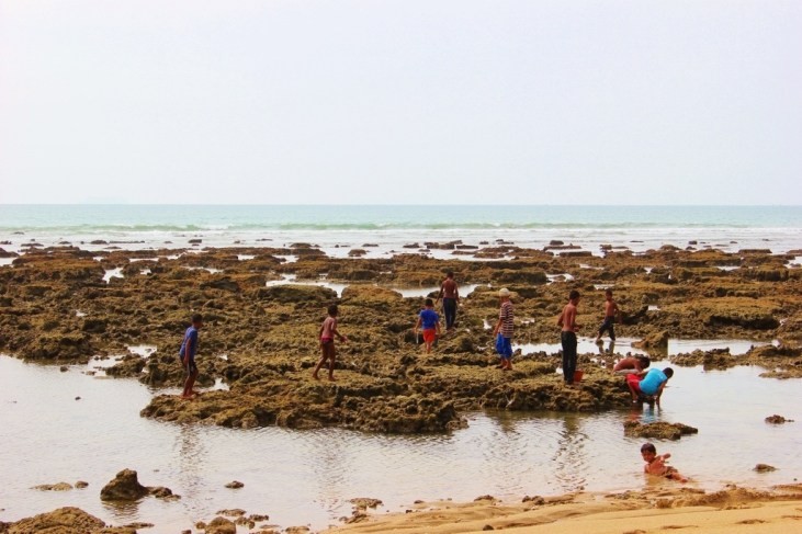 Kids play on exposed rocks at low tide on Klong Khong Beach in Koh Lanta, Thailand