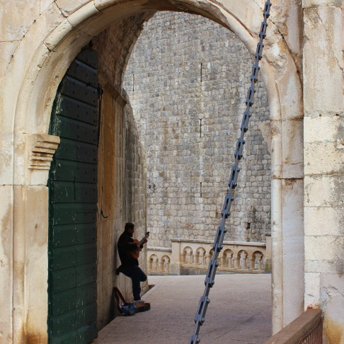 Man playing guitar at Pile Gate in Dubrovnik, Croatia