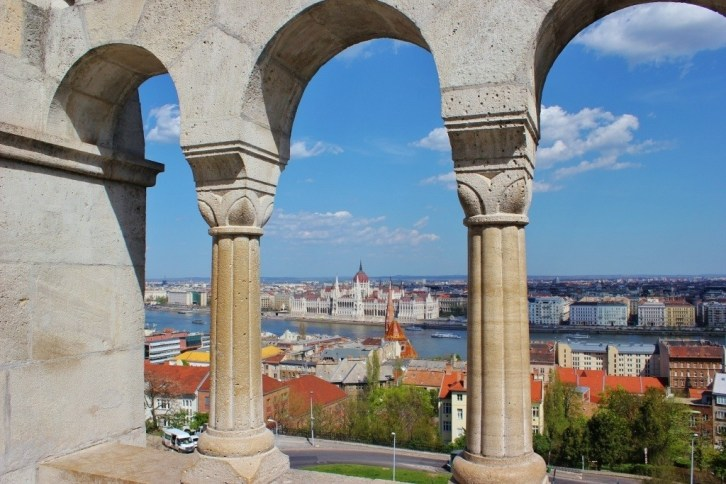 Castle Hill sights: Fisherman's Bastion arched arcade with a peek at the Parliament Building across the Danube River.