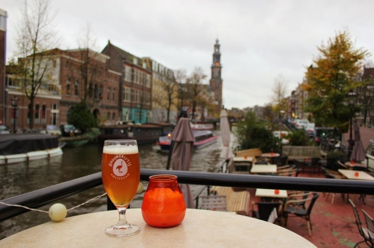 Glass of craft beer on Amsterdam canal, Netherlands
