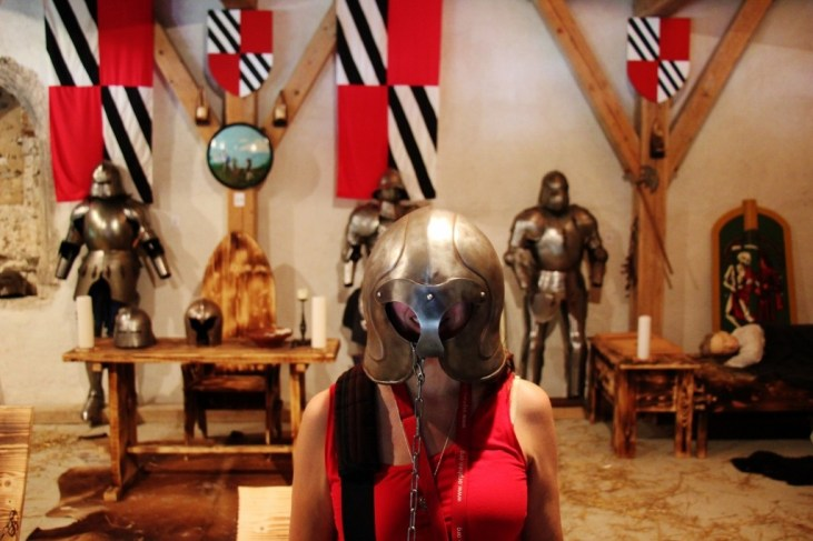 Sarah wearing armor in the Armor Room at Predjama Castle, Slovenia