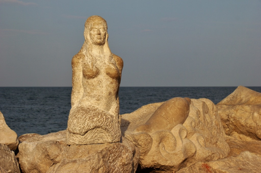 Mermaid and dolphin sculptures on point in Piran, Slovenia