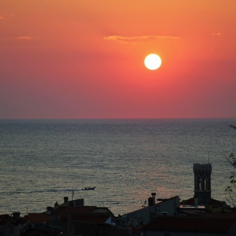Round sun at sunset off point of Piran, Slovenia