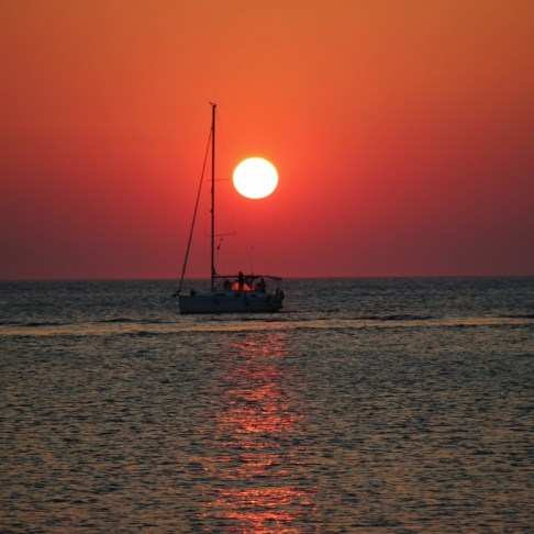Orange ball sun at sunset with sailboat, Piran Slovenia