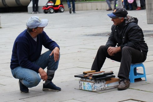 Man talks to shoeshiner on Mother Teresa Boulevard in Prishtina, Kosovo