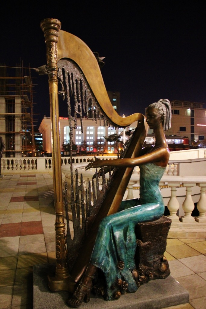 Statue of woman playing decaying harp, Skopje, Macedonia