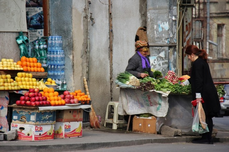 Woman buys vegetables from Old Town produce street vendor, Tbilisi, Georgia
