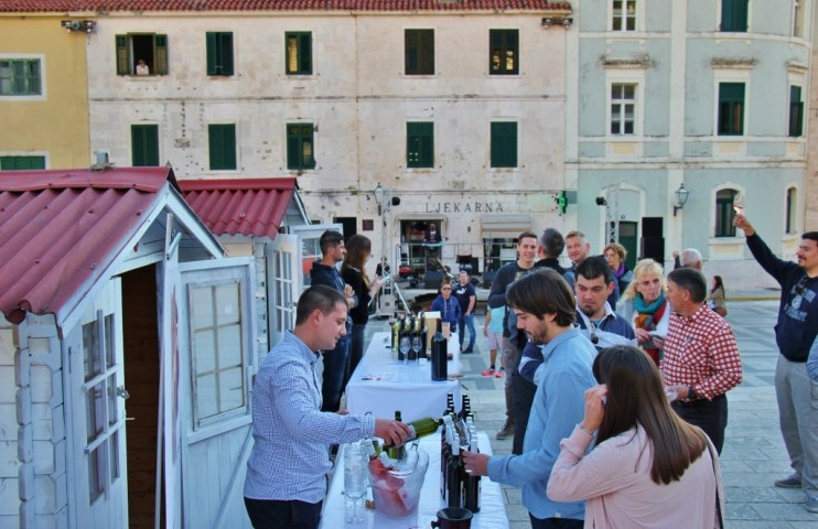 Vendor pours wine at wine festival on Kacic Square, Makarska, Croatia