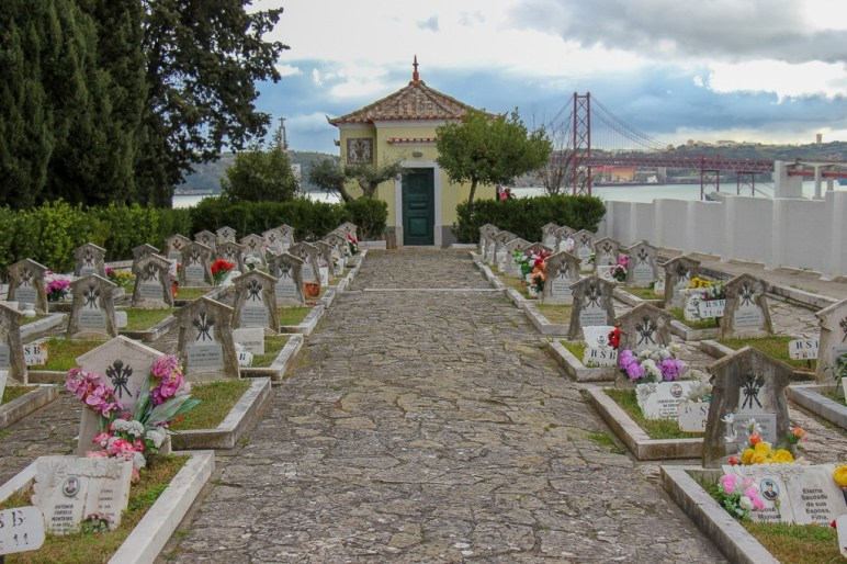 Graves decorated with flower and a view of the tagus river from Cemiterio dos Prazeres, Lisbon, Portugal