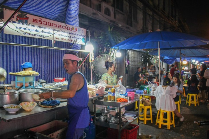 Busy cook at outdoor food stall in Chinatown, Bangkok, Thailand