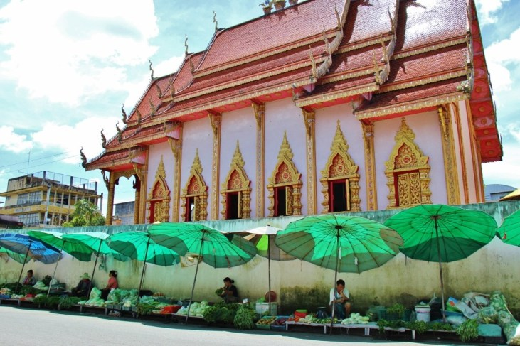 Produce vendors line the sidewalk in front of a temple in Chiang Rai, Thailand