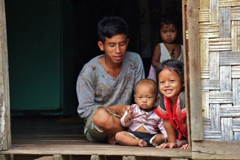 Family in doorway in Ban Houy Pha Lam, Laos