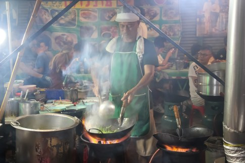 Chef cooks over flaming fire at Fikeaw in Chinatown, Bangkok, Thailand