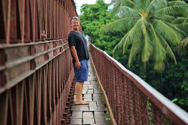 Crossing the Old Bridge via pedestrian walkway in Luang Prabang, Laos