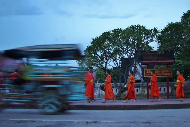 Tuk tuk drives past monks walking in Morning Almsgiving Ceremony in Luang Prabang, Laos