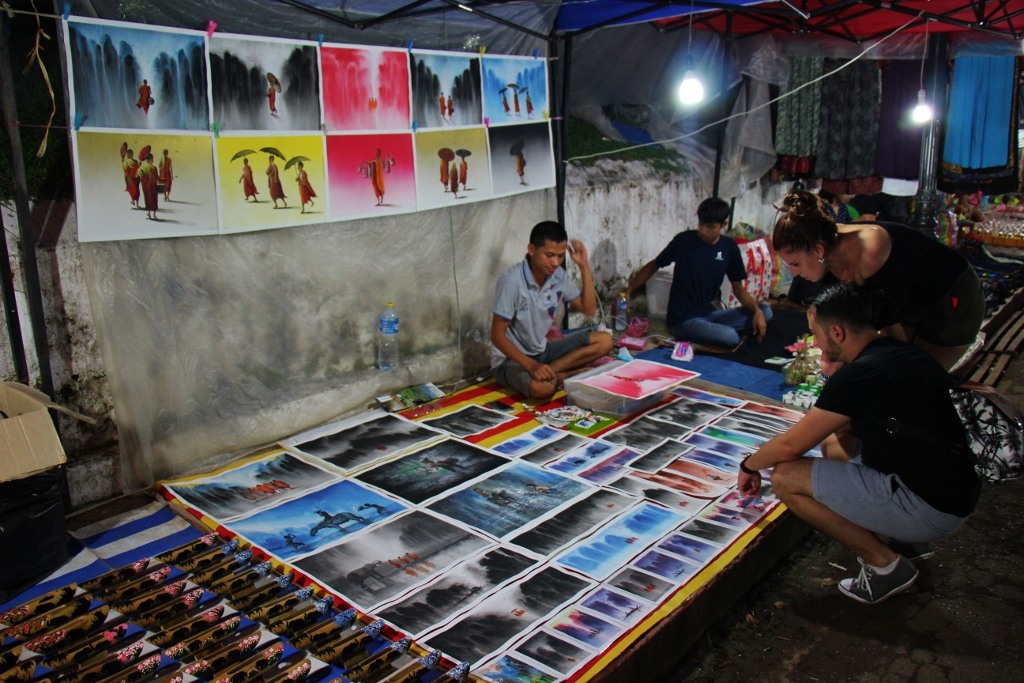 Man sells his paintings at Night Market in Luang Prabang, Laos