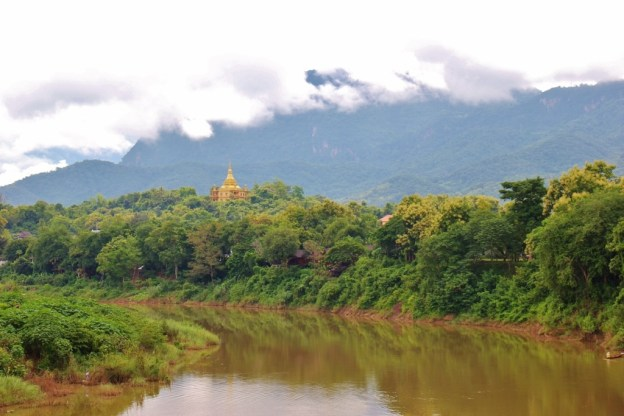 View of Nam Khan River and hillside temple from Old Bridge, Luang Prabang, Laos