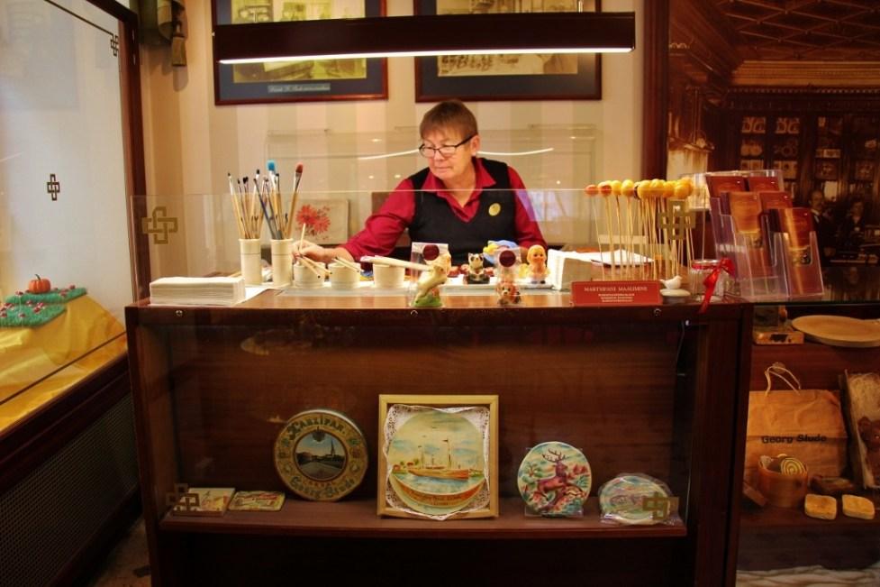 Woman paints marzipan in workshop at Kalev Marzipan Museum in Tallinn, Estonia