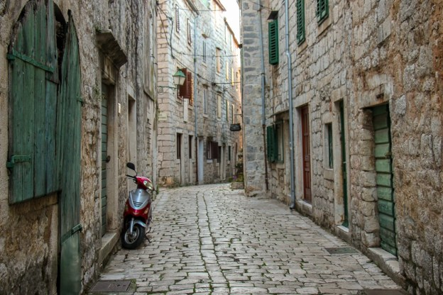 Scooter in Stari Grad Old Town stone lane on Hvar Island, Croatia