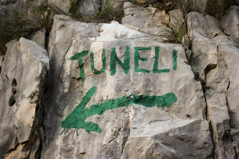 Green-Painted Tuneli sign pointing way to Tito's Cave in Stari Grad on Hvar Island, Croatia