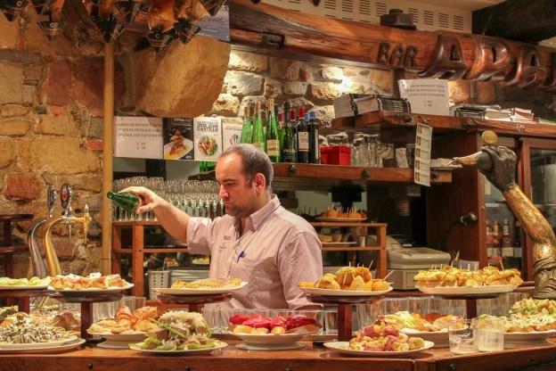 Bartender pouring Basque Country wine at La Cepa Pintxos Bar in San Sebastian, Spain
