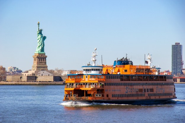 Staten Island Ferry passes by Statue of Liberty in New York City, New York