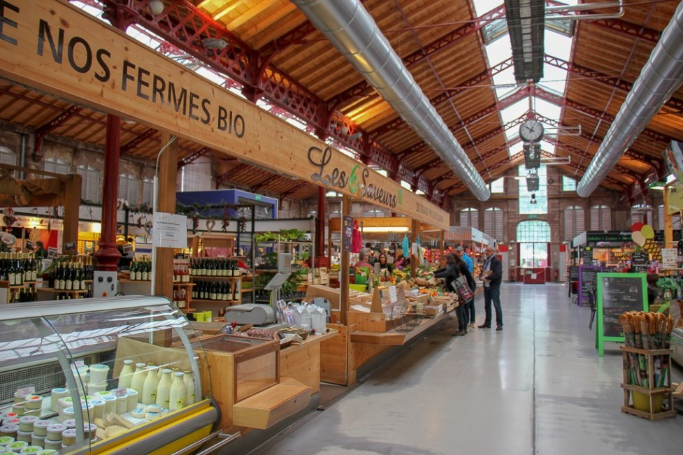 Fresh produce and cheese stalls at Covered Market Halle in Colmar, France